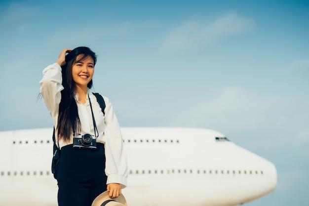 Femme heureuse avec caméra en attente de voyage en avion.