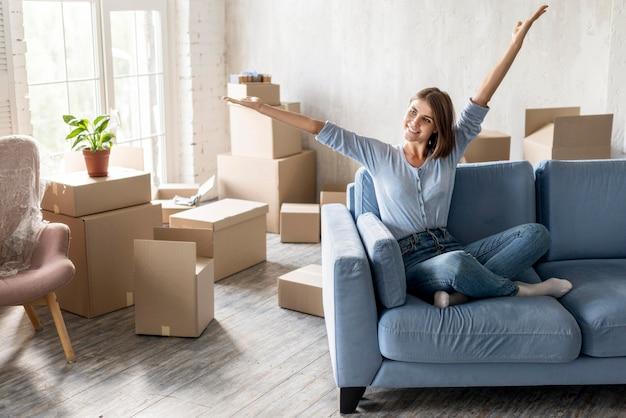 Femme heureuse sur le canapé déménageant avec des boîtes prêtes