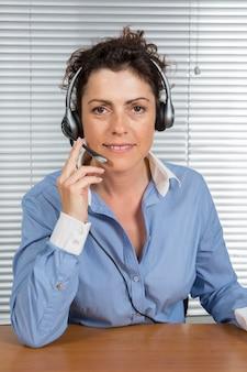 Femme heureuse, à, casque à écouteurs, à, elle, bureau, à, client