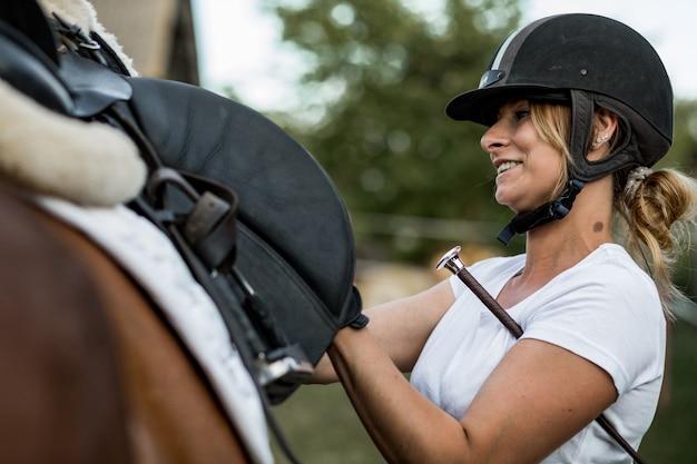 Une femme heureuse en casque de sport communique avec son cheval avant l'entraînement.