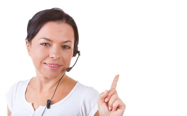 Une femme heureuse avec un casque travaillant au centre d'appels montre la direction du doigt vers l'espace de copie pour votre conception sur fond blanc