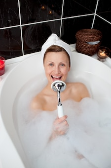 Femme heureuse chantant dans un bain moussant