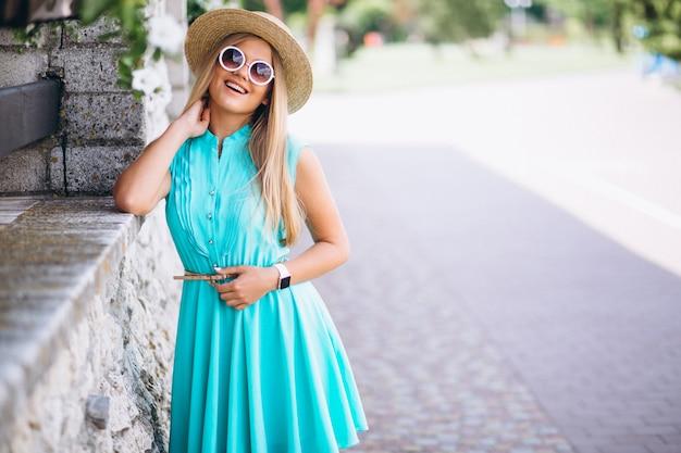 Femme heureuse en chapeau et bleu s'habiller dans le parc
