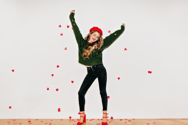 Femme heureuse en chaussures à talons hauts rouges dansant sur un mur blanc sous des confettis coeur