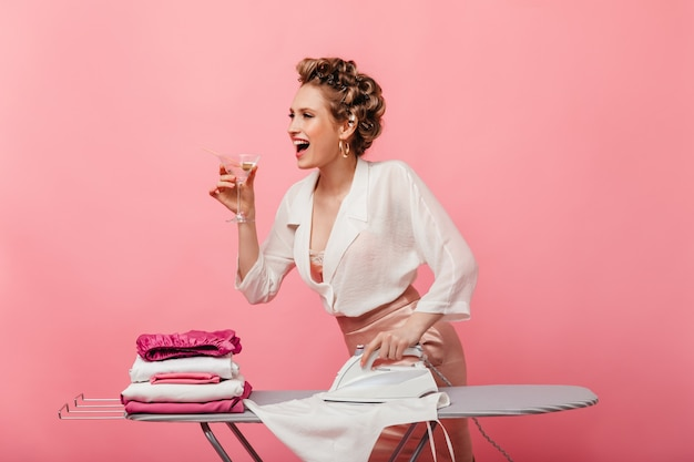 Femme heureuse en chemisier blanc et jupe rose tenant le verre à martini et le fer