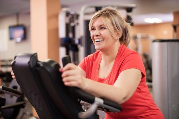 Femme heureuse à cheval sur un vélo d'exercice dans la salle de sport