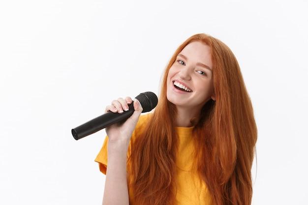 Femme heureuse, à, cheveux bouclés, chant, quoique, tenue, microphone, isolé, sur, blanc