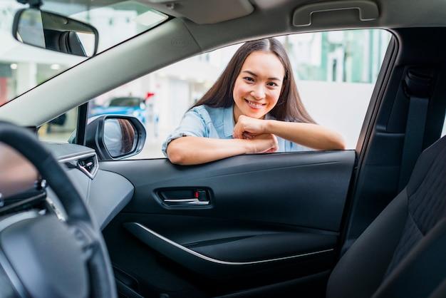 Femme heureuse chez un concessionnaire automobile