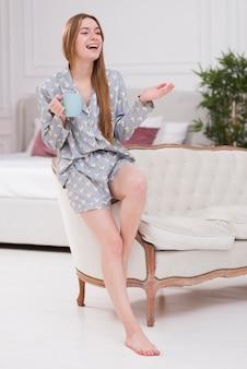 Femme heureuse, chez soi, à, tasse thé