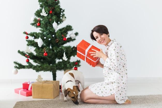 Femme heureuse avec chien ouvrant des cadeaux de noël. sapin de noël avec des cadeaux en dessous. décoré