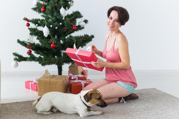 Femme heureuse avec chien ouvrant des cadeaux de noël