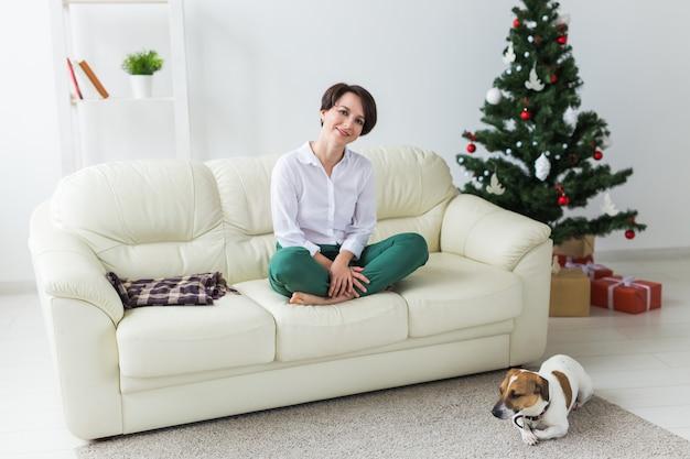 Femme heureuse avec chien. sapin de noël avec des cadeaux en dessous. salon décoré