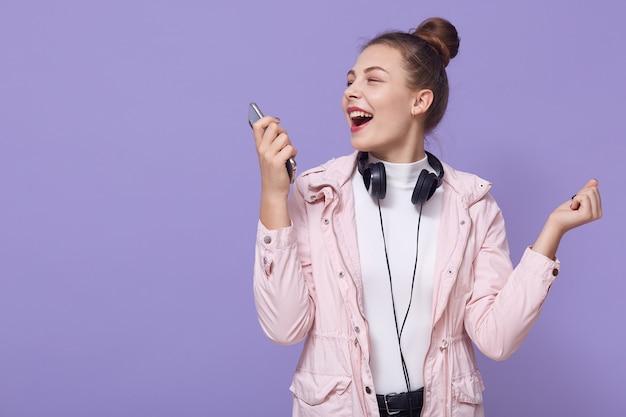 Une femme heureuse avec un chignon apprécie la fin heureuse de la journée, écoute de la musique joyeuse dans les écouteurs, tient le téléphone et chante la chanson, vêtue d'une veste rose pâle et d'une chemise blanche, a des écouteurs autour du cou.