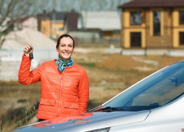 Femme heureuse avec les clés en main sur la voiture à la maison