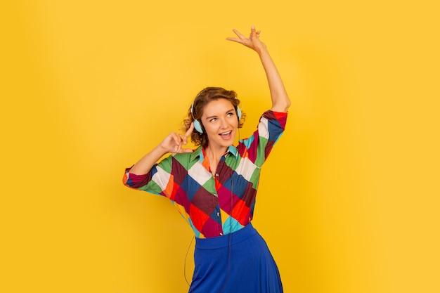 Femme heureuse avec une coiffure courte écoutant de la musique avec des écouteurs et s'amusant sur un mur jaune