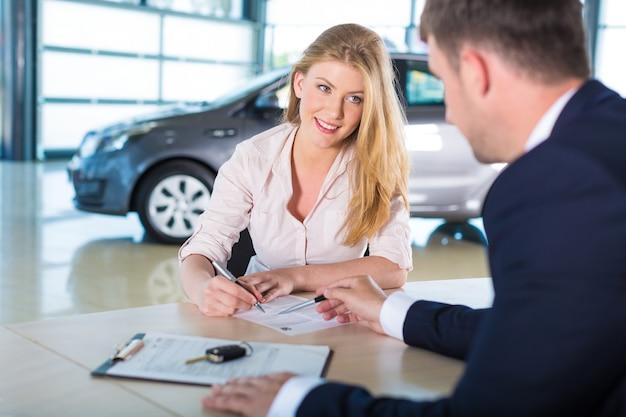Femme heureuse avec un concessionnaire automobile dans un salon de l'auto ou un salon