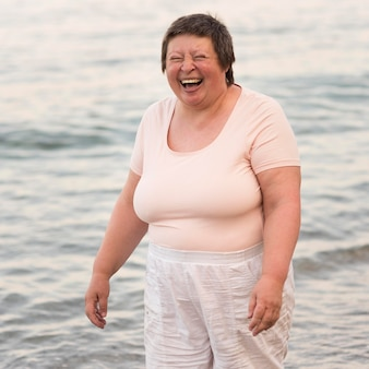 Femme heureuse coup moyen au bord de la mer