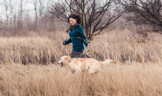 Femme heureuse en cours d'exécution avec un beau chien dans la nature