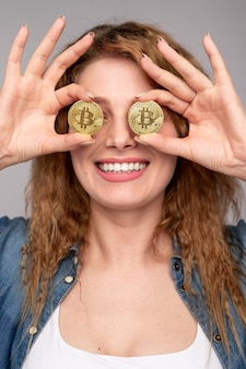 Femme heureuse couvrant les yeux avec des bitcoins brillants