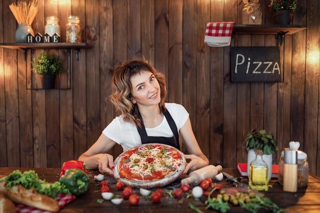 Femme heureuse, cuisine pizza, chez soi