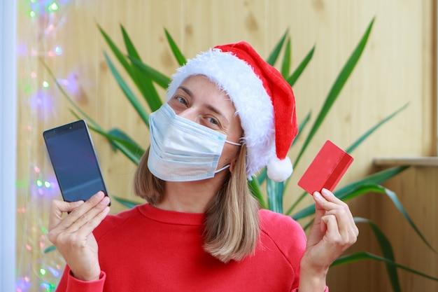 Une femme heureuse dans un bonnet de noel rouge et un masque médical fait une commande en ligne et paie