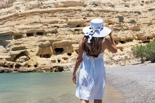 Femme heureuse dans un chapeau sur une plage tropicale.