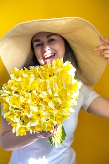 Une femme heureuse dans un chapeau avec un tas de jonquilles jaunes