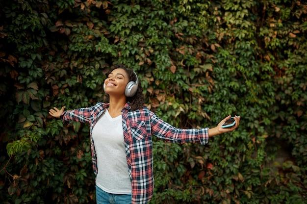 Femme heureuse dans les écouteurs, écouter de la musique dans le parc d'été. fan de musique féminine marchant à l'extérieur, fille dans les écouteurs, buissons verts