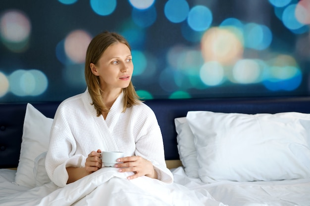 Femme heureuse, dans lit, à, a, tasse café