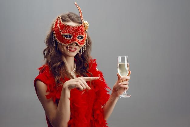 Femme heureuse dans un masque de carnaval rouge et boa avec un verre de champagne surélevé