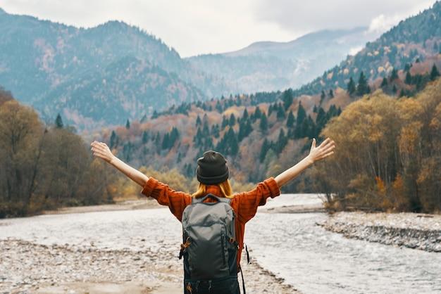 Femme heureuse dans les montagnes se déplace près de la rivière dans la nature et a levé les mains