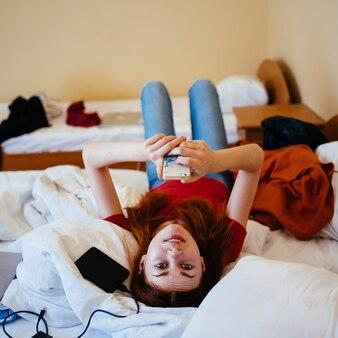 Femme heureuse dans un t-shirt rouge et un jean se trouve dans son lit avec un téléphone portable dans ses mains.