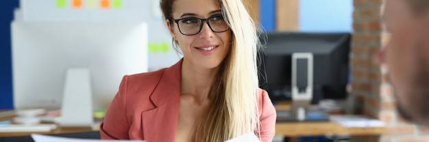 Femme heureuse dans des verres aux cheveux longs tenir le dossier dans sa main, regarder le directeur et écouter. l'homme est assis au bureau en face d'un collègue et examine le document avec diagramme.