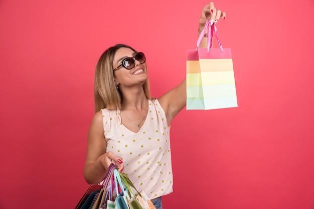 Femme heureuse dans des verres tenant ses sacs à provisions.