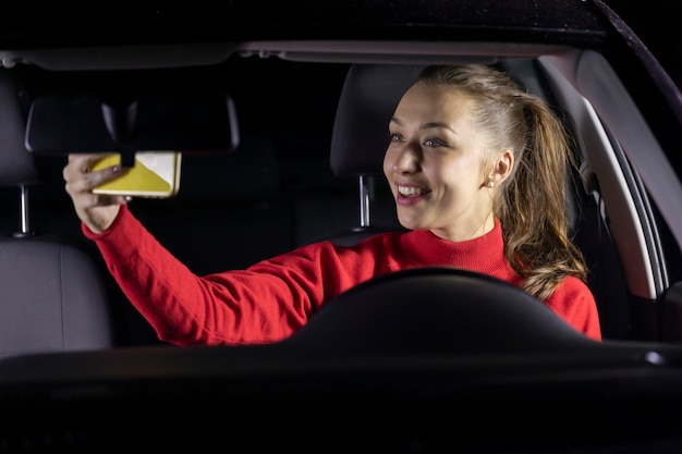 Femme heureuse dans la voiture la nuit s'est arrêtée garée et fait des appels vidéo à la famille