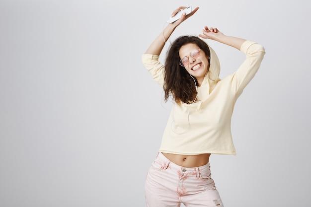 Femme heureuse dansant et appréciant la musique dans les écouteurs, tenant le smartphone