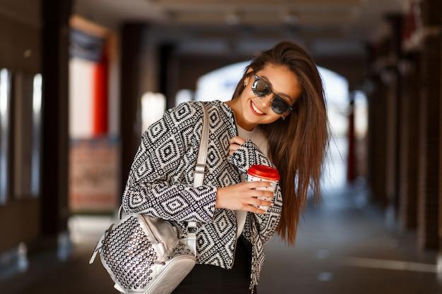 Femme heureuse avec du café dans des vêtements de mode avec un sac se promène dans la ville