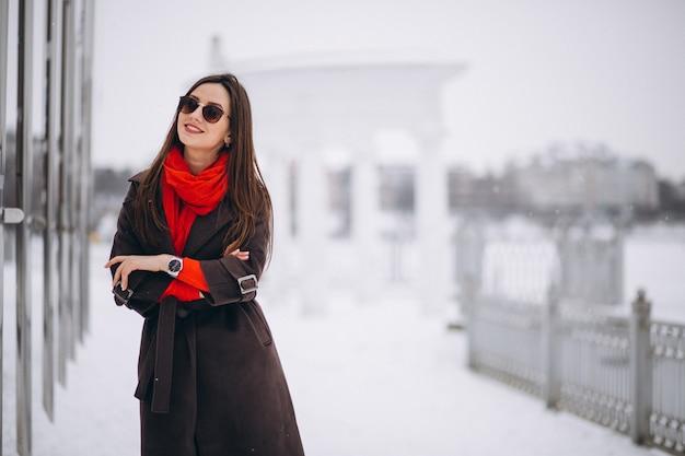Femme heureuse en écharpe rouge en hiver à l'extérieur