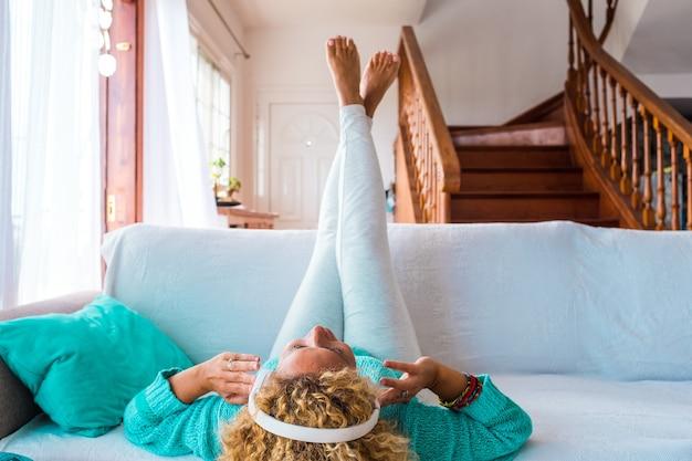 Une femme heureuse écoutant de la musique et dansant à la maison à l'aide d'un casque allongé sur le canapé ou le canapé - profitant de la musique
