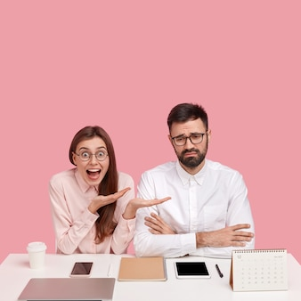 Une femme heureuse émotionnelle positive attire l'attention sur un jeune homme d'affaires frustré qui fait face à un problème financier, assis ensemble au bureau blanc avec des gadgets électroniques, du café et du bloc-notes. travail en équipe