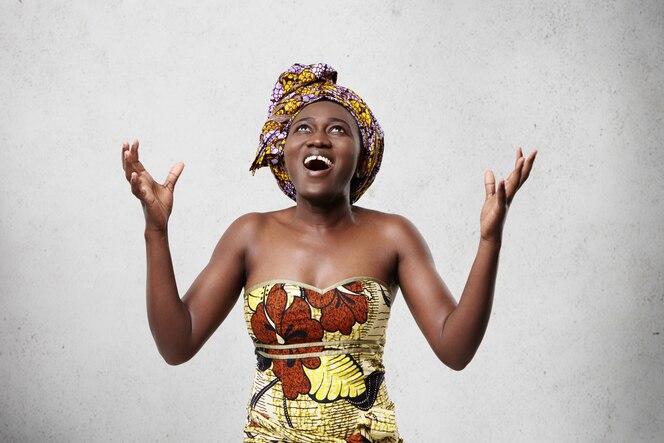 Femme heureuse énergique avec une peau foncée portant un foulard sur la tête et une robe à la mode en levant les mains avec excitation en étant reconnaissante à dieu pour avoir sauvé la vie. heureuse femme africaine d'âge moyen