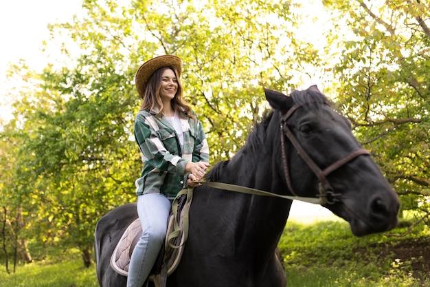 Femme heureuse équitation cheval coup moyen