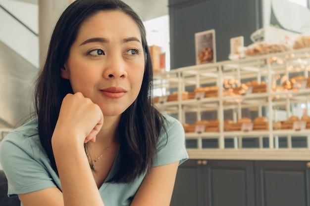Une femme heureuse est assise et attend quelqu'un dans le café de la boulangerie.