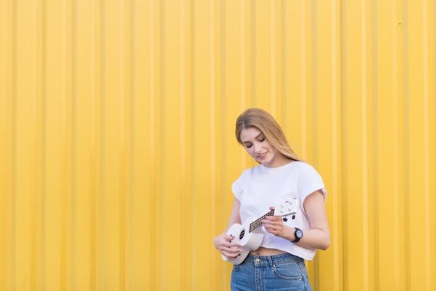 Une femme heureuse est sur un mur jaune, joue du ukulélé et sourit. concept musical. jouer sur des instruments de musique