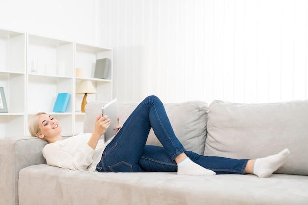 La femme heureuse était allongée sur le canapé et tenait une tablettej