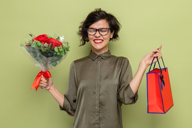Femme heureuse et excitée aux cheveux courts tenant un bouquet de fleurs et un sac en papier avec des cadeaux souriant joyeusement