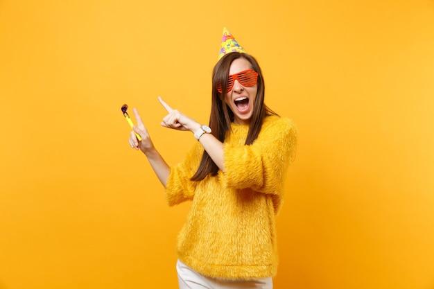 Femme heureuse excitée dans des lunettes orange drôles, chapeau d'anniversaire avec pipe en train de pointer les index de côté sur l'espace de copie, célébrant isolé sur fond jaune. les gens émotions sincères, mode de vie.