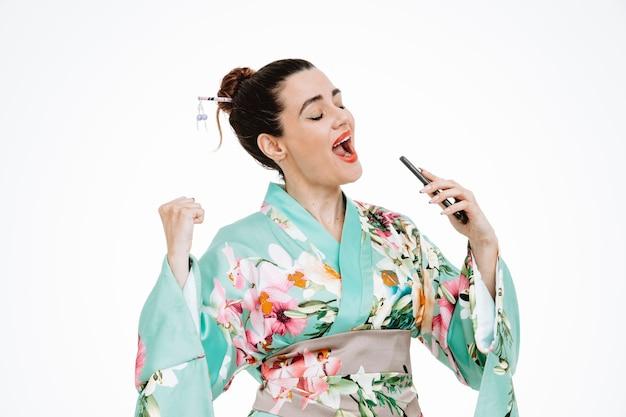 Femme heureuse et excitée en kimono japonais traditionnel tenant un smartphone l'utilisant comme microphone chantant une chanson s'amusant sur blanc