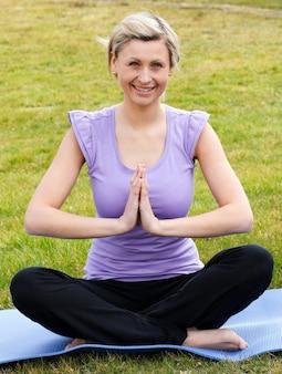 Femme heureuse, faire du yoga dans un parc
