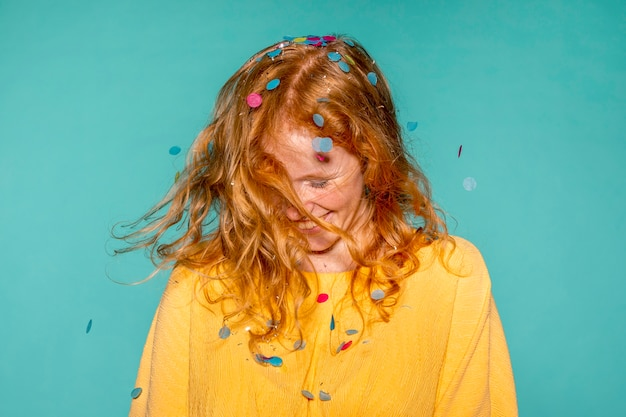 Femme heureuse faire la fête avec des confettis dans ses cheveux